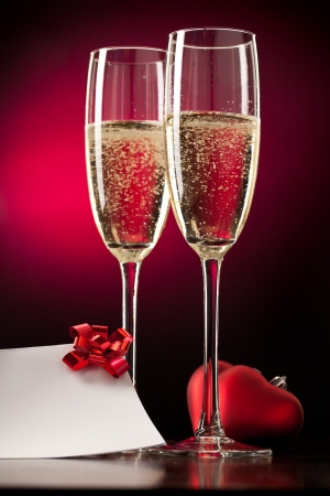 Two full glasses of champagne over red background Stock Photo - 8617877