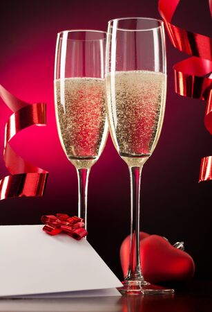 Two full glasses of champagne over red background Stock Photo - 8618075