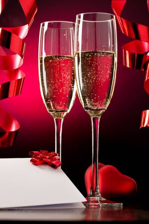 champagne flutes: Two full glasses of champagne over red background Stock Photo