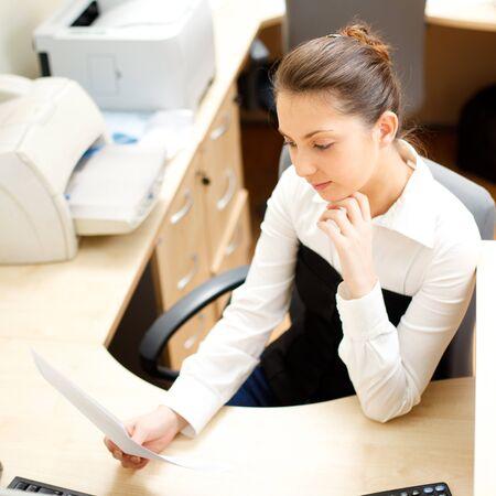 docs: Beautiful woman reading docs in office