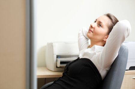 Beautiful woman sitting in the chair and  relaxing at office photo