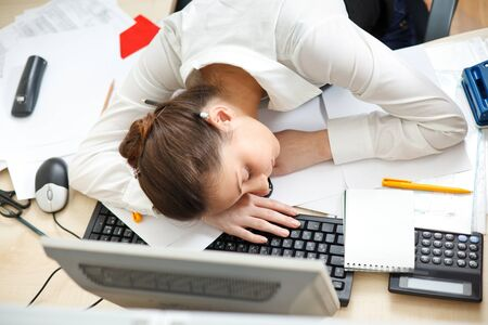 Office life. Young woman sleeping at workplace.