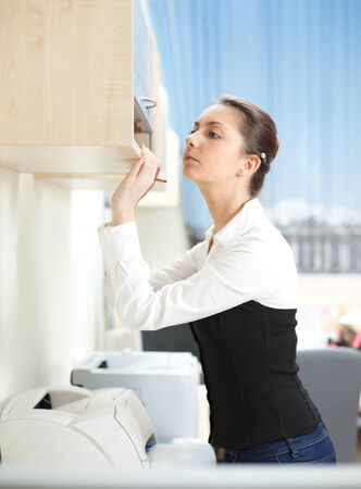 Office life. Woman searches for documents on a shelf. photo