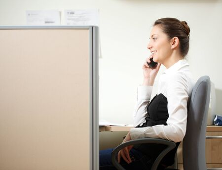 Woman talking over the phone in the office photo