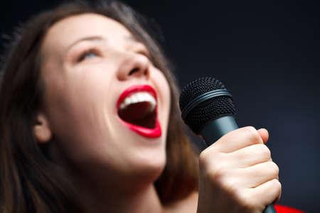 pop singer: Woman sing over dark background. focused on hand.