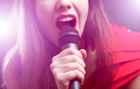 female singer: Woman sing over color background. Focused on arm. Stock Photo