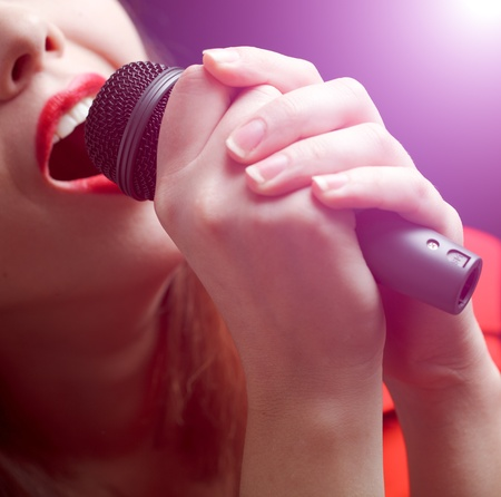 Woman sing over color background. Focused on microphone photo
