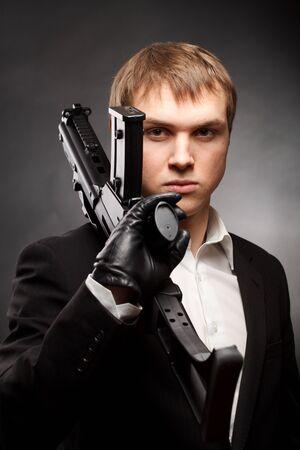 sicario: Hombre de pistola sobre gris degradado Foto de archivo