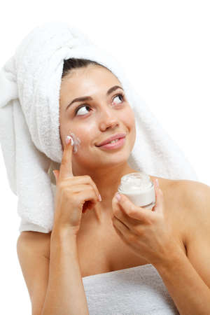 Beautiful women applying moisturizer cosmetic cream on face. Isolated over white. photo