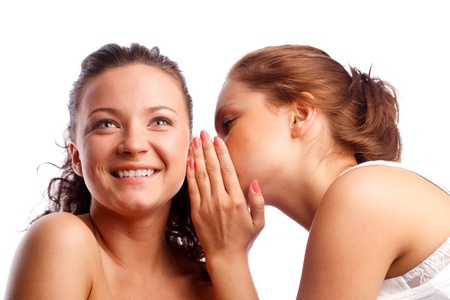 Young woman whispering something to her frind. Isolated over white. Stock Photo - 9754789