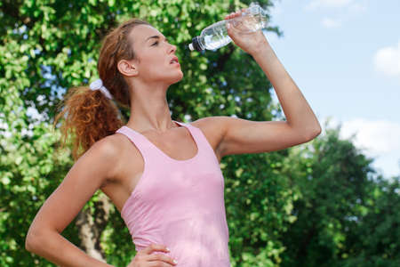Woman drink water after jogging photo
