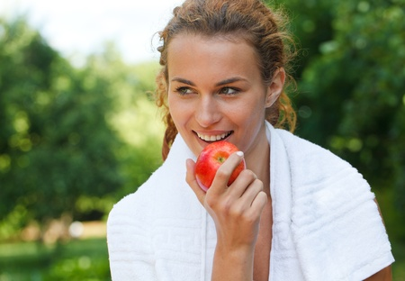 Young woman after sport workout eating apple photo
