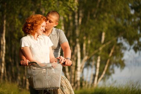 Young couple sitting at one bicycle Stock Photo - 9996646