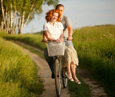 Happy young couple riding on a bicycle Stock Photo - 9996654