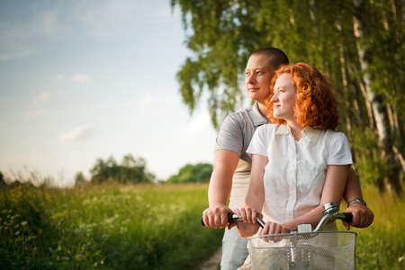 Young couple sitting one bicycle and looking at something Stock Photo - 9996610