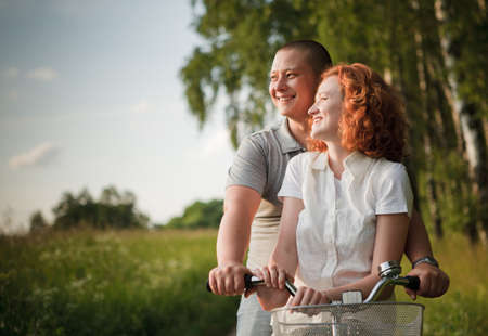 Young couple sitting one bicycle and looking at something Stock Photo - 9996657
