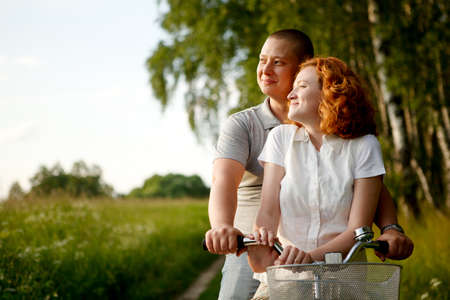 Young couple sitting one bicycle and looking at something Stock Photo - 9996592