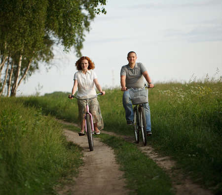 Happy young couple riding on a bicycles photo