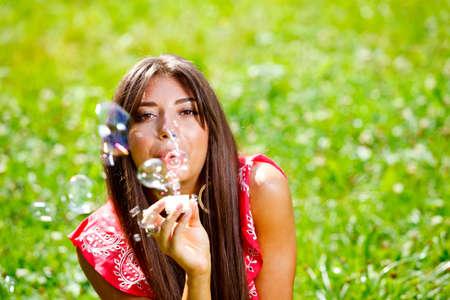 Beautiful woman blowing soap bubbles photo