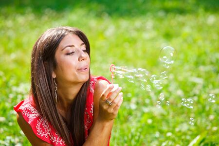 Beautiful woman blowing soap bubbles Stock Photo - 9996614