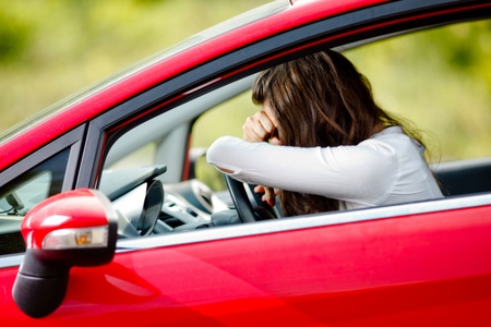 traffic accidents: Young woman sitting depressed in car