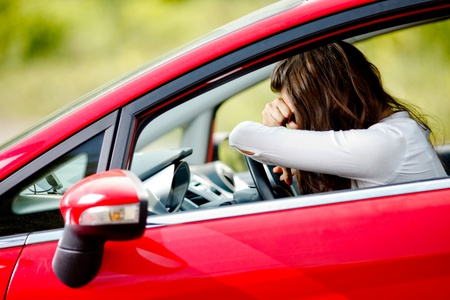 Young woman sitting depressed in car photo