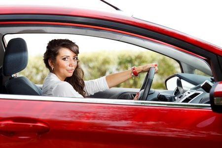 new motor vehicles: Young pretty woman in the red car