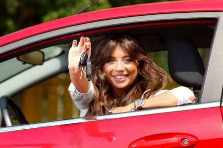 car keys: Beautiful young  woman in the new car with keys