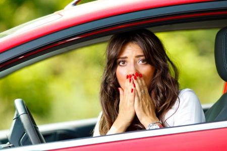 accidente transito: Mujer joven y bonita miedo sentado en el coche rojo