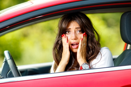 Young pretty scared woman in the car Stock Photo