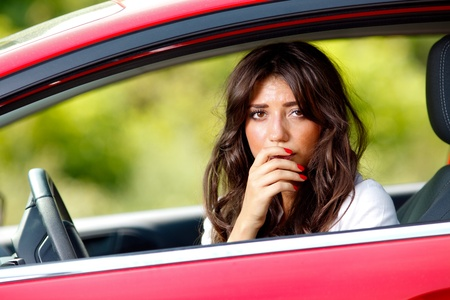 Young pretty scared woman in the car photo