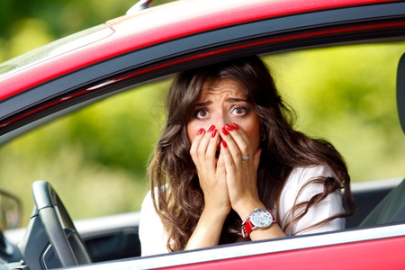 is astonished: Young pretty scared woman in the car Stock Photo
