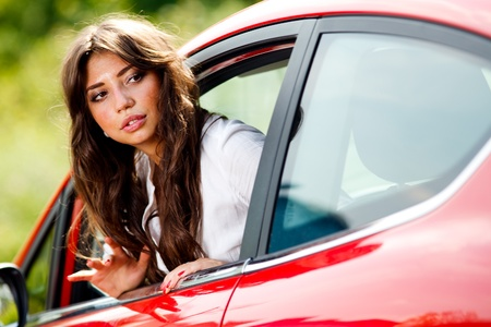 Young pretty woman looking at back of car photo
