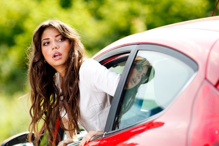 bad accident: Young pretty woman looking at back of car