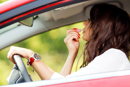 Woman doing makeup while driving photo