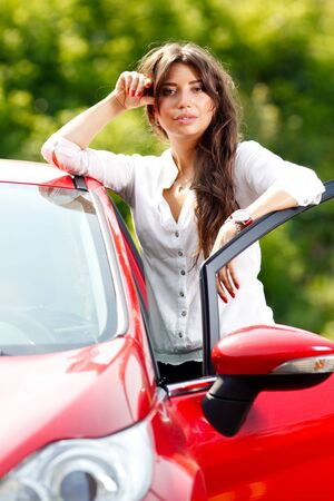 Young pretty woman in the red car photo