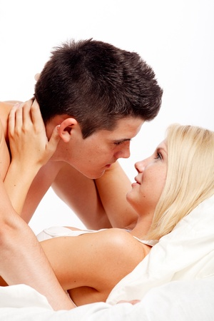 Loving affectionate heterosexual couple on bed. photo