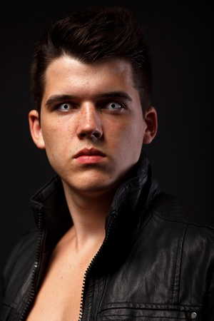 Portrait of young man over dark background.