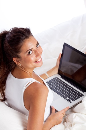 Woman with laptop lying in bed photo