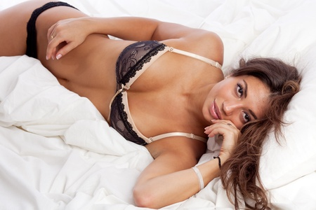 portrait of beautiful smiling young woman lying in bed in her underwear. Stock Photo - 10586249