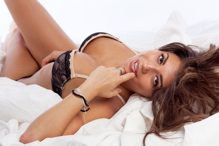 portrait of beautiful smiling young woman lying in bed in her underwear. Stock Photo - 10586258