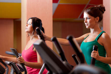 aerobic exercise: Young women in gym on stepper machine