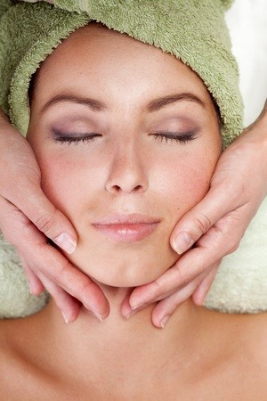 body care: Young woman receiving facial massage