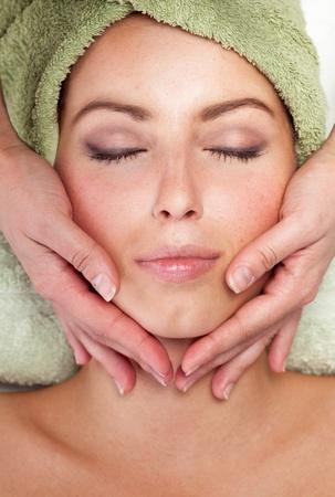 Young woman receiving facial massage photo