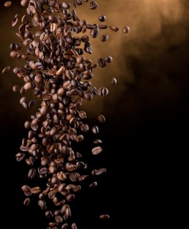 Flying coffee beans over dark