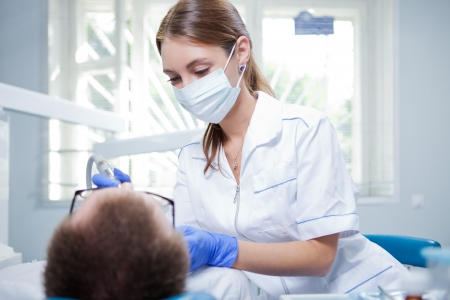 gloves women: A young female dentist working in her office  Stock Photo