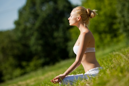 Young girl doing yoga in the park photo