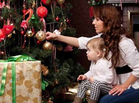 Happy mother decorating christmas tree with her baby photo