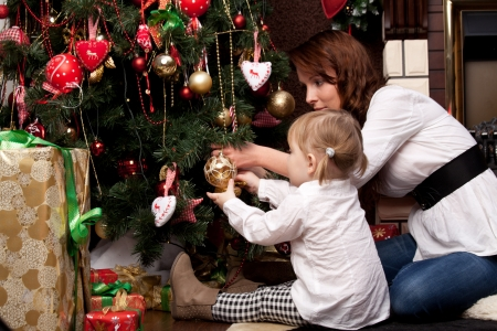 Happy mother decorating christmas tree with her baby