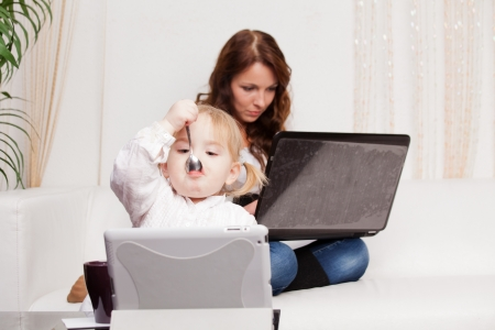 Madre y beb� con la computadora port�til photo